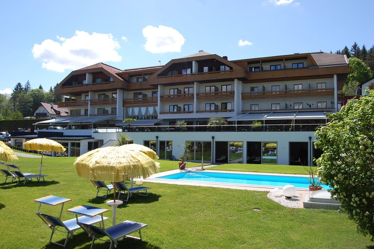 Exterior of the hotel with the green gardens, pool and hotel
