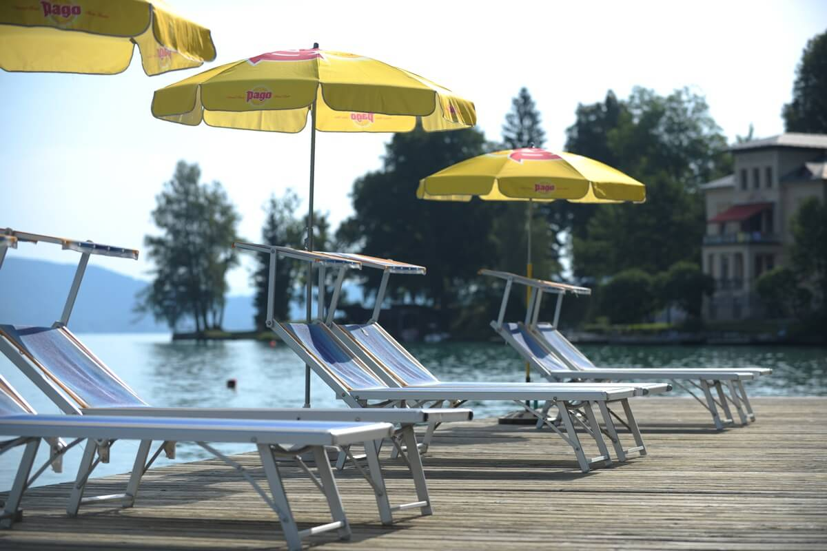 Footbridge with loungers and parasols with a view of Lake Wörthersee