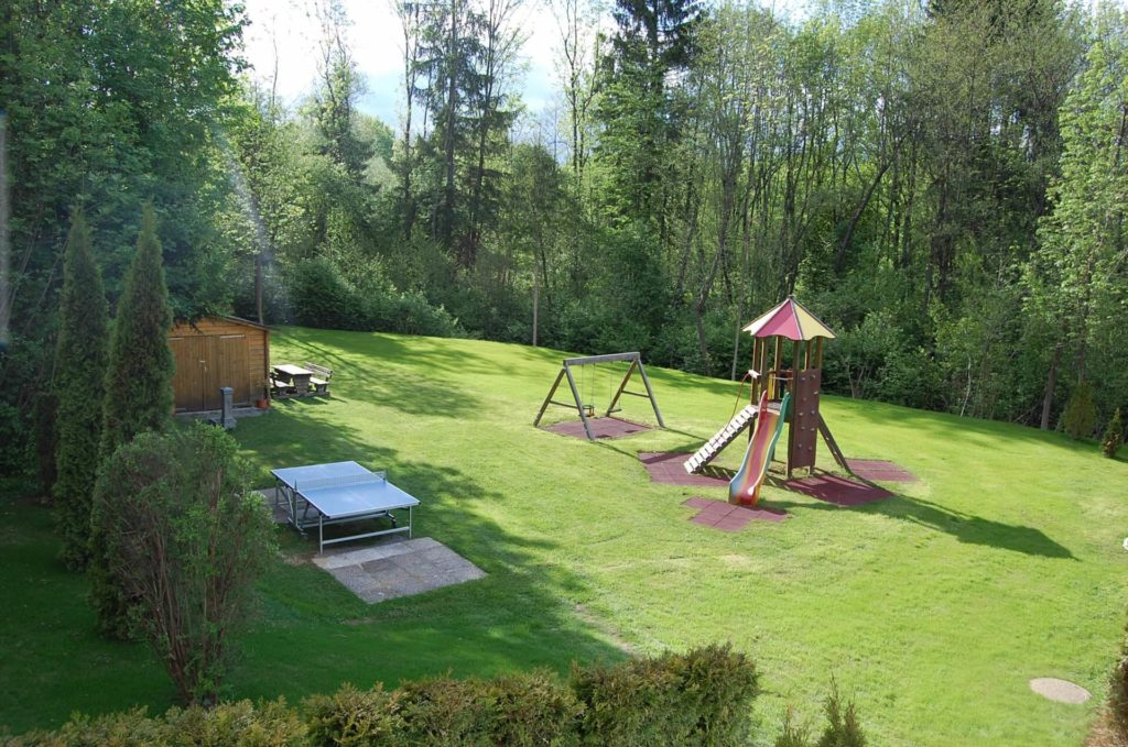 Children's playground with slide, swing, small climbing tower and table tennis table
